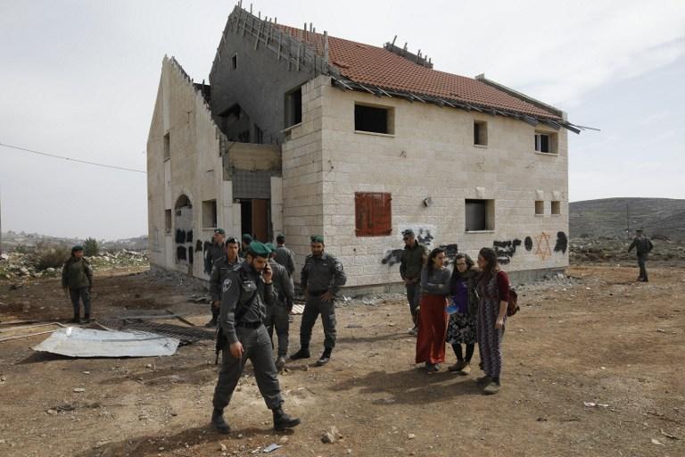 Gardes-frontières et jeunes manifestants devant une maison devant être démolie dans l'implantation d'Ofra, en Cisjordanie, le 27 février 2017. (Crédit : Menahem Kahana/AFP)