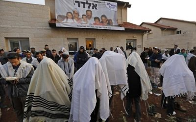 De jeunes militants de droite prient devant une maison qui doit être évacuée et démolie dans l'implantation d'Ofra, en Cisjordanie, le 28 février 2017. (Crédit : Menahem Kahana/AFP)