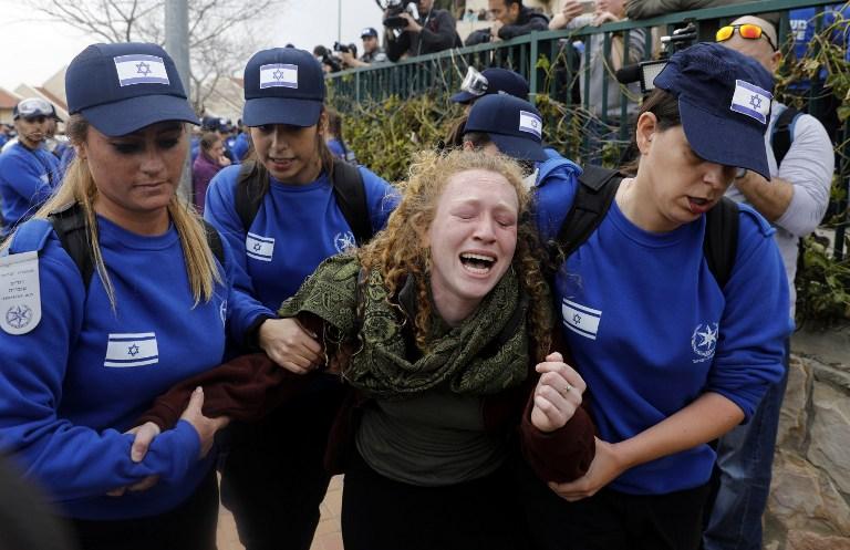 La police évacue une manifestante de l'implantation d'Ofra, le 28 février 2017. (Crédit : Menahem Kahana/AFP)