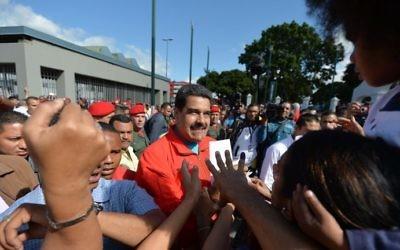 Le président vénézuélien Nicolas Maduro (au centre) entouré de sympathisants alors qu'il arrive au bureau de vote lors des élections législatives, à Caracas, le 6 décembre 2015 (Crédit : AFP PHOTO / LUIS ROBAYO / AFP / LUIS ROBAYO)