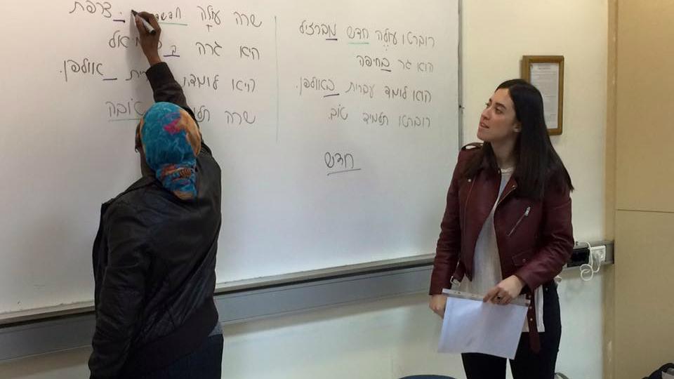 Le professeur bénévole Julia Aharon (à droite), étudiante à l'Institut de technologie, regarde l'une de ses élèves, un agent d'entretien du Centre médical Wolfson, écrire sur le tableau lors d'un cours d'hébreu de l'organisation ERETZ en janvier 2017 (Crédit : (Renee Ghert-Zand/TOI)