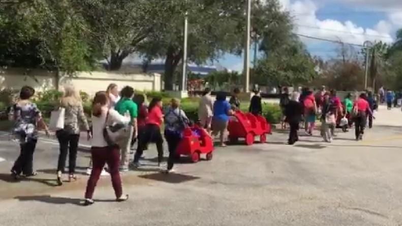 Elèves et employés d'une école juive rentrent dans les locaux après une évacuation pour une menace à la bombe à Davie, en Floride, le 27 février 2017. (Crédit : capture d'écran Twitter/Erica Rakow)