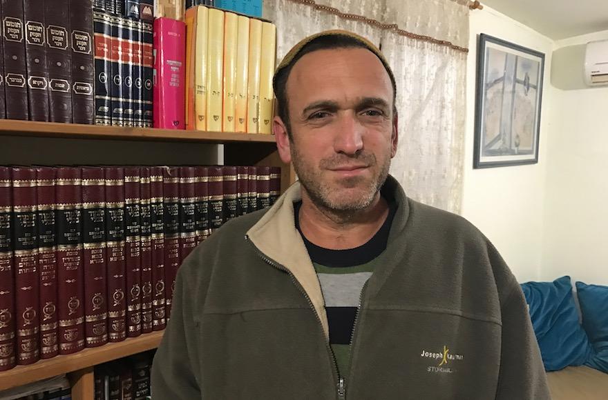 Elad Ziv dans son salon à Amona, le 30 janvier 2017 (Crédit : Andrew Tobin/JTA)