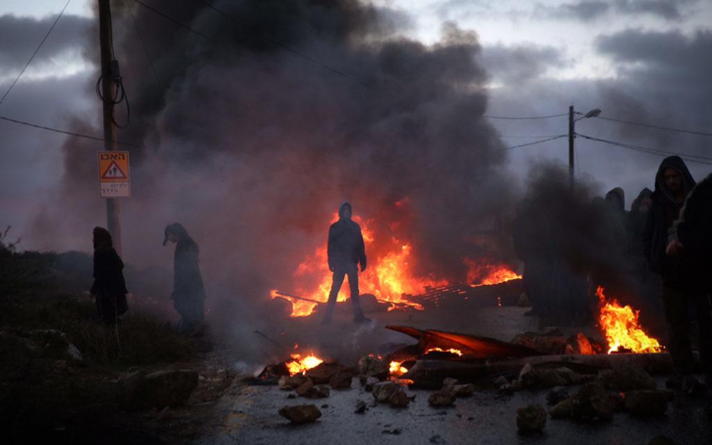 Des manifestants brûlent des pneus à l'entrée de l'avant-poste d'Amona, en Cisjordanie, le 1er février 2017. (Crédit : Hadas Parush/Flash90)