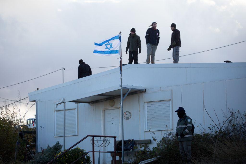 Des Israéliens sur un toit pendant l'évacuation de l'avant-poste d'Amona, en Cisjordanie, le 1er février 2017. (Crédit : Miriam Alster/Flash90)