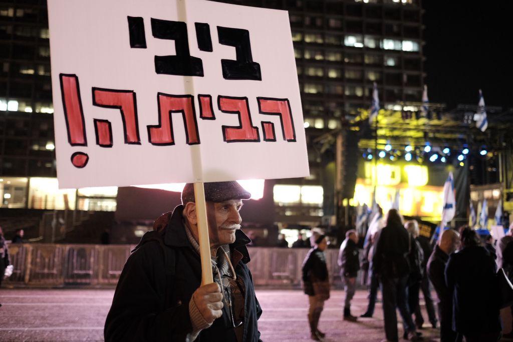 """Un Israélien portant un panneau """"Bibi, rentre chez toi"""" participe à une manifestation contre le Premier ministre Benjamin Netanyahu à Tel Aviv, le 2 février 2017  (Crédit : Tomer Neuberg/Flash90)"""