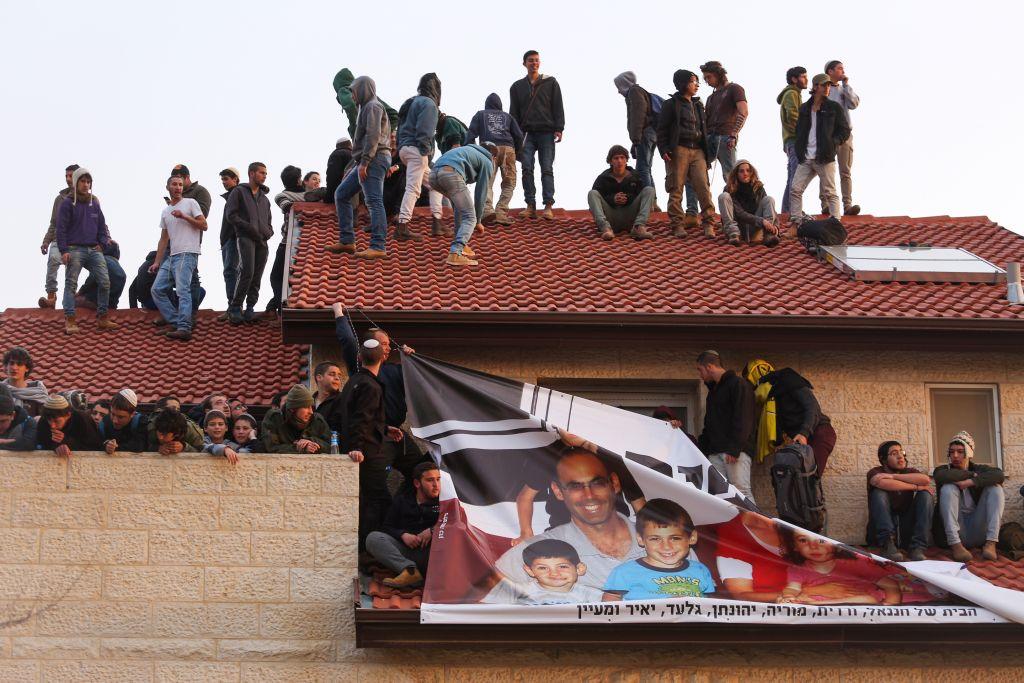 Des manifestants sur le toit d'une maison pendant l'opération d'évacuation de neuf maisons dans l'implantation d'Ofra, en Cisjordanie, le 28 février 2017. (Crédit : Hadas Parush/Flash90)