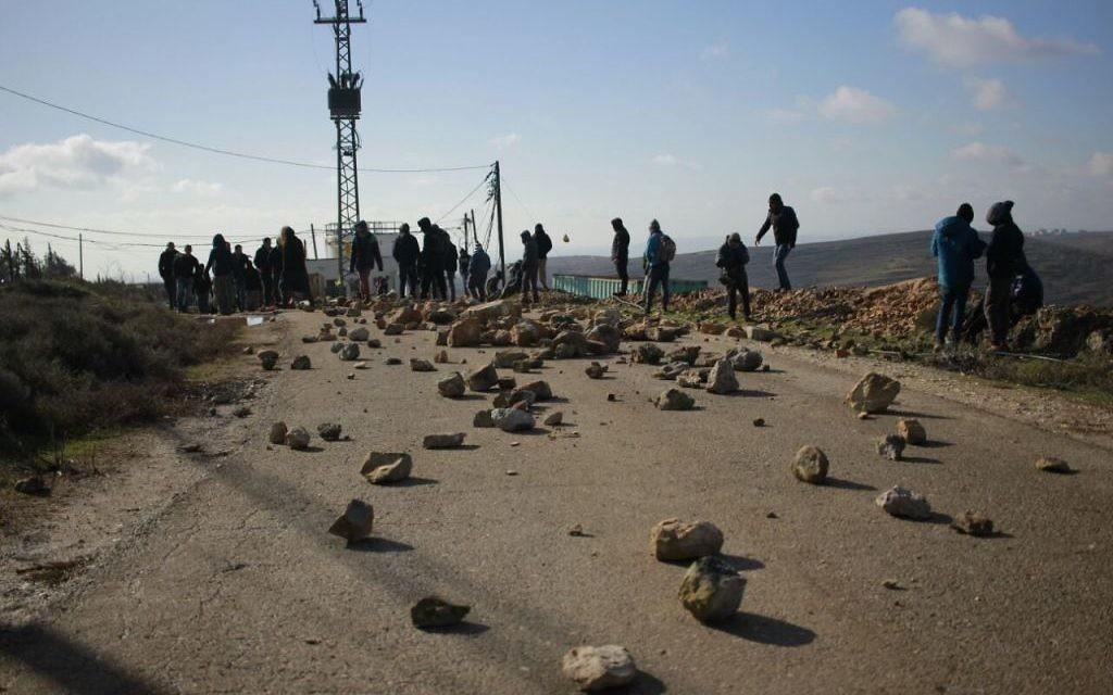Des manifestants israéliens placent des rochers sur la route menant à l'avant-poste de Cisjordanie d'Amona, avant son démantèlement, le 1er février 2017. (Crédit : Judah Ari Gross/Times of Israël)