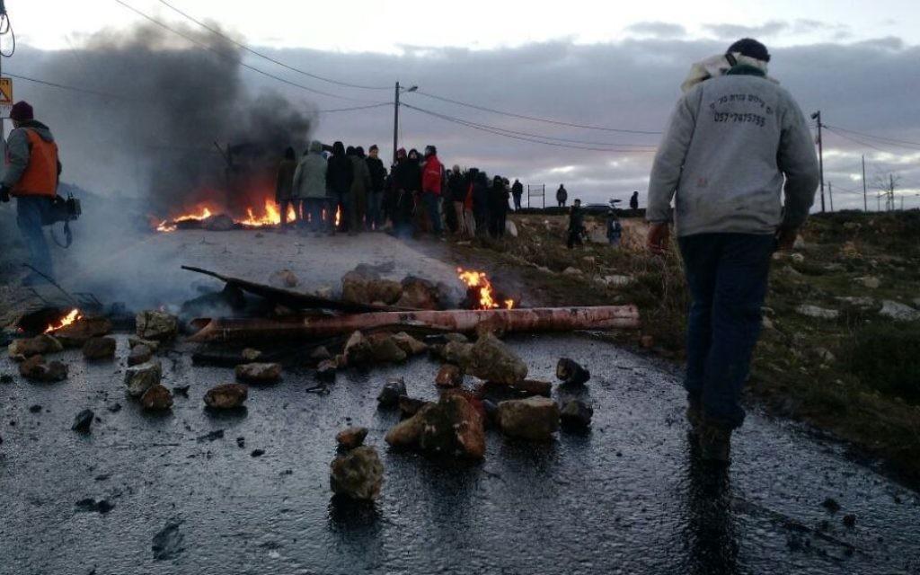 Des partisans des implantations brûlent des pneus et d'autres objets à l'entrée de l'avant-poste d'Amona, en Cisjordanie, le 1er février 2017. (Crédit : Judah Ari Gross)