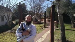 L'ancien habitant de l'avant-poste d'Amona Avraham Rossana avec son bébé de trois mois sur le campus du séminaire d'Ofra, le 2 février 2017 (Crédit : Raoul Wootliff/Times of Israel)