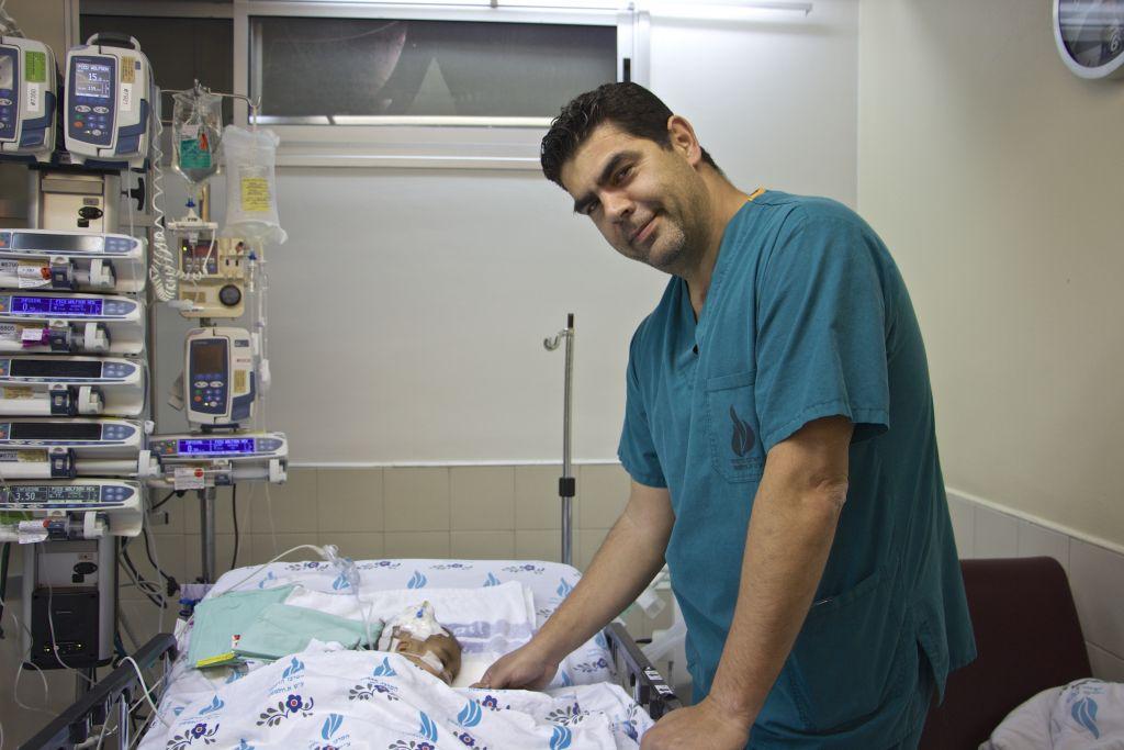 Le docteur Hagi Dekel, chirurgien cardiaque israélien du centre médical  Wolfson à Holon, aux côtés de  Yacub, un petit garçon de deux ans dont il a sauvé la vie, le 23 février 2017 (Crédit : Dov Lieber/Times of Israel)