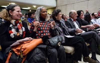 Les participants se tiennent la main lors d'une rencontre interconfessionnelle organisée à la synagogue Loop de Chicago, quelques jours après un acte de vandalisme antisémite dans l'édifice, le 8 février 2017 (Crédit : Robert Kusel)