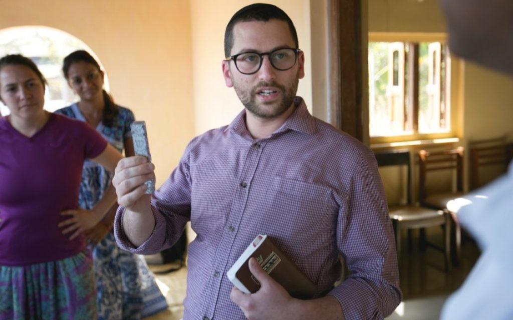 Rabbi James Proops fixe une Mezouzah au quartier général du Gabriel Project à Ashte. (Autorisation)
