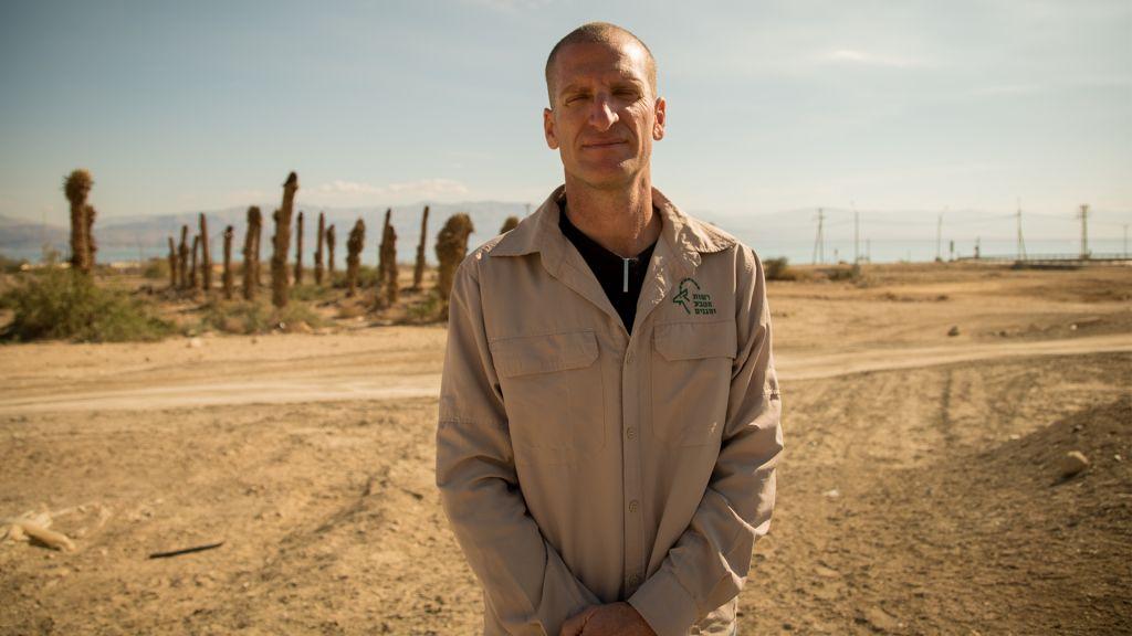 Harel Ben Shahar, drecteur de la région Arava de l'Autorité de la nature et des parcs d'Israël, qui comprend la réserve naturelle d'Ein Gedi, devant un verger de dattes abandonné, le 3 janvier 2017. (Crédit : Luke Tress/Times of Israël)