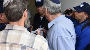 Des policiers parlent aux manifestants et aux habitants des neuf maisons qui ont été construites illégalement dans l'implantation d'Ofra, en Cisjordanie, et doivent être démolies, le 28 février 2017. (Crédit : police israélienne)