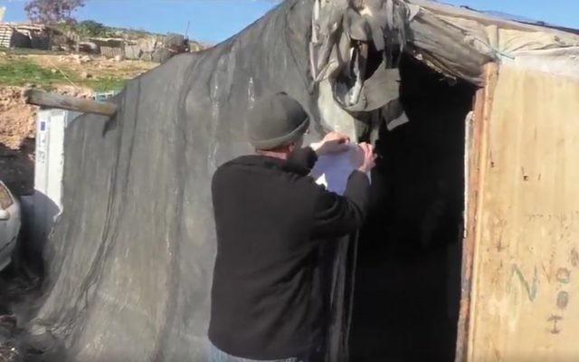 Des soldats israéliens accrochent des ordres de démolition sur une structure illégale dans le campement bédouin de Khan al-Ahmar, au nord-est de Jérusalem, en février 2017. (Crédit : capture d'écran Twitter)