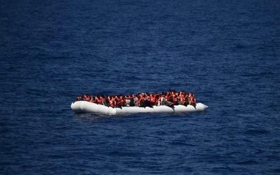 Des réfugiés sur un canot attendent d'être secourus, le 24 mai 2016. Illustration. (Crédit : Gabriel Bouys/AFP)