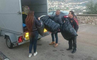 Des volontaires israéliens emballant des fournitures d'hiver qui devraient être livrés aux réfugiés syriens (Crédit : Opération Chaleur Humaine)
