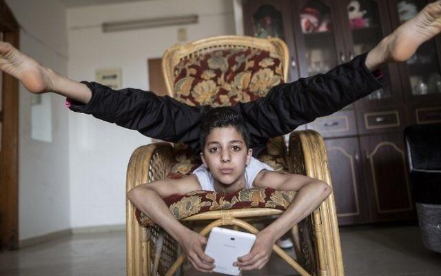 Une photo prise le 28 avril 2016 de Mohammed al-Sheikh, alors âgé de douze ans, l'adolescent palestinien montrant ses talents de contorsionniste à son domicile dans la ville de Gaza (Crédit ; AFP PHOTO / MAHMUD HAMS)