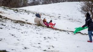 Des Israéliens profitent de la neige sur le plateau du Golan, le 28 janvier 2017 (Crédit : Basel Awidat/Flash90)