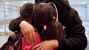 Fadi Kassar embrasse ses deux petites filles, qu'il n'a pas vu depuis deux ans, après avoir retrouvé sa famille à l'aéroport JFK de New York, le 2 février 2017. (Crédit : Bill Swersey/HIAS)