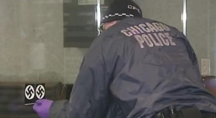 Un agent de police enlève un autocollant représentant une croix gammée sur la porte de la synagogue Loop de Chicago le 4 février 2017. La police estime qu'il s'agit d'un crime de haine. (Capture d'écran : NBC Chicago)