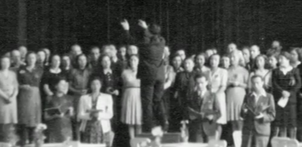 Seule photographie connue des détenus de Theresienstadt chantant le Requiem de Verdi, prise pendant la dernière représentation le 23 juin 1944. Raphael 'Rafi' Schachter dirige la chorale, devant un public où était présent Adolf Eichmann et une délégation de la Croix Rouge internationale. (Crédit : Fondation Terezin)