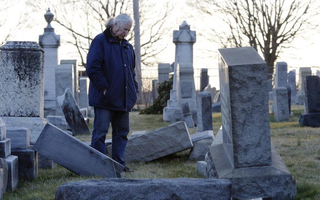Un homme devant les pierres tombales profanées du cimetière juif du mont Carmel à Philadelphie, le 26 février 2017. (Crédit : Dominick Reuter/AFP)