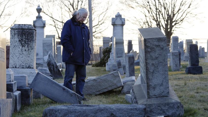 Un homme regarde les pierres tombales renversées dans le cimetière juif du mout Carmel à Philadelphie, le 26 février 2017. (Crédit : Dominick Reuter/AFP)