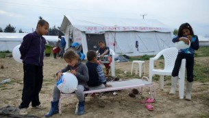 """Des enfants réfugiés jouent près d'une tente où figure le slogan """" nous voulons aller en Allemagne"""", dans un camp de réfugiés Idomeni, le 1er mai 2016. Illustration. (Crédit : Gili Yaari/Flash90)"""