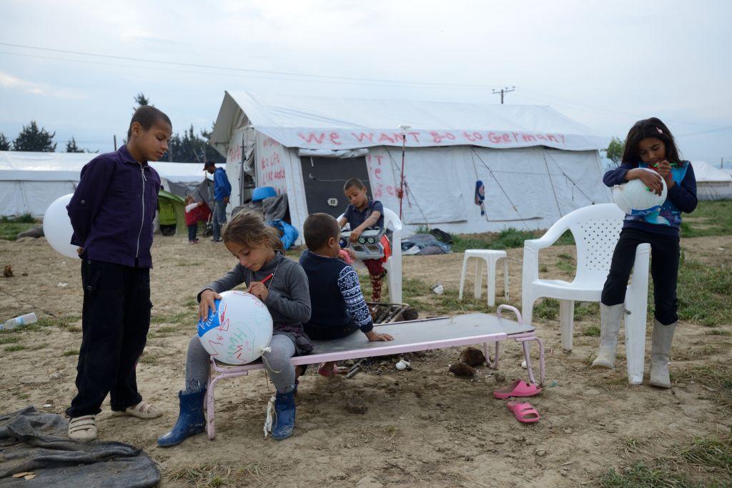 """Des enfants réfugiés jouent près d'une tente où figure le slogan """" nous voulons aller en Allemagne,dans un camp de réfugiés Idomeni, le 1 mai 2016. (Crédit : Gili Yaari/Flash90)"""