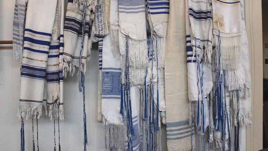 Un rang de châles de prière à la Congrégation Bnai Israel montre le style unique de tzitzit utilisé par les Juifs karaïtes. (Crédit : David A.M. Wilensky)