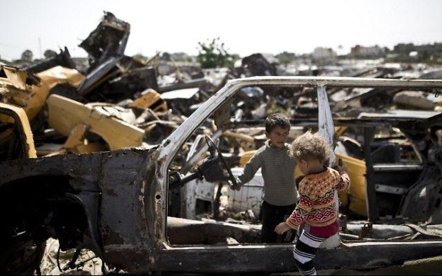 Des enfants palestiniens jouent dans des véhicules abandonnés dans une zone appauvrie dans la ville de Khan Yunis, dans le sud de la bande de Gaza, le 26 avril 2016 (Crédit : AFP / Mahmud Hams)