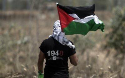 """Un jeune Palestinien brandit son drapeau alors que l'armée israélienne cherche des tunnels à la frontière est de Gaza Ville, le 15 mai 2016, le jour du 68e anniversaire de la Nakba, la """"catastrophe"""" de la création de l'Etat d'Israël. (Crédit : Mahmud Hams/AFP)"""