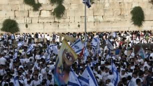 Des Israéliens réunis au mur Occidental dans la vieille ville de Jérusalem le 5 juin 2016 avec des drapeaux célébrant le Jerusalem Day, qui marque la victoire d'Israël lors de la guerre des Six jours de 1967 (Menahem Kahana/AFP)