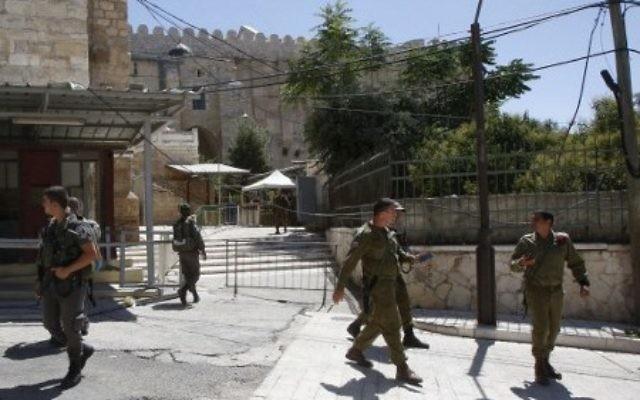 Forces de sécurité devant l'entrée du Tombeau des Patriarches, à Hébron, en Cisjordanie, le 1er juillet 2016. (Crédit : Hazem Bader/AFP)