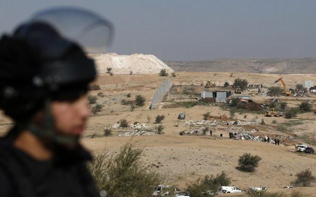 Un policier israélien en train de protéger les bulldozers qui détruisent des maisons dans le village bédouin d'Umm al-Hiran, dans le désert du Néguev, le 18 janvier 2017. (Crédit : Menahem Kahana/AFP)