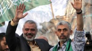 Ismail Haniyeh, alors chef du Hamas dans la bande de Gaza, à gauche, avec Yahya Sinwar, l'un des fondateurs de la branche armée du groupe terroriste, à l'arrivée des détenus libérés en échange du soldat Gilad Shalit, à Khan Yunis, le 21 octobre 2011. (Crédit : Said Khatib/AFP)