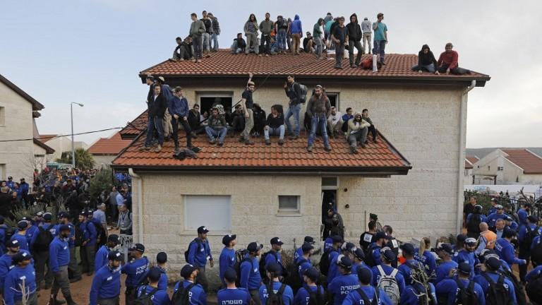 Evacuation des manifestants de l'implantation d'Ofra, en Cisjordanie, le 28 février 2017. (Crédit : Menahem Kahana/AFP)