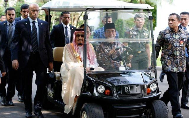 Le roi Salmane d'Arabie saoudite, à gauche, conduit par le président indonésien Joko Widodo dans une voiture de golf au palais présidentiel de Jakarta, le 2 mars 2017. (Crédit : Darren Whiteside/Pool/AFP)