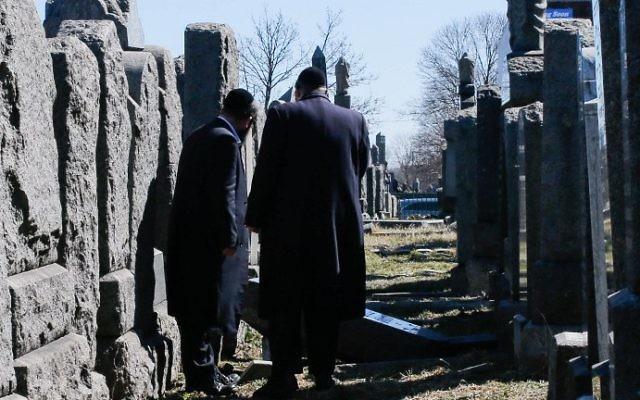 Les membres de la communauté juive inspectent les pierres tombales qui ont été renversées dans le  Washington Cemetery de New York, dans le quartier de Brooklyn, le 5 mars 2017 ( Crédit : AFP PHOTO / EDUARDO MUNOZ ALVAREZ)