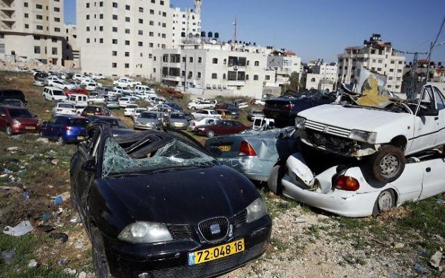 Epaves de voitures avec des plaques d'immatriculation israéliennes dans le village d'al-Ram, en Cisjordanie, le 6 mars 2017. (Crédit : Abbas Momani/AFP)