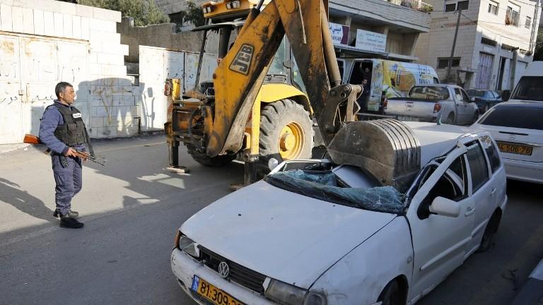 Un bulldozer détruit une voiture portant une plaque d'immatriculation israélienne dans le village d'al-Ram, en Cisjordanie, le 6 mars 2017. (Crédit : Abbas Momani/AFP)