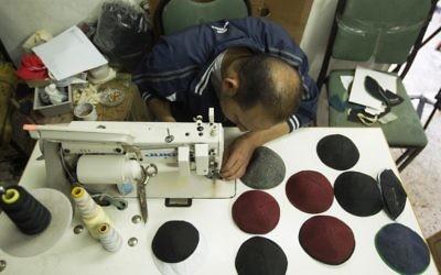 Un Palestinien travaillant dans une usine textile de Gaza fabriquant des kippas, le 8 mars 2017 (Crédit : AFP / Mahmud Hams)