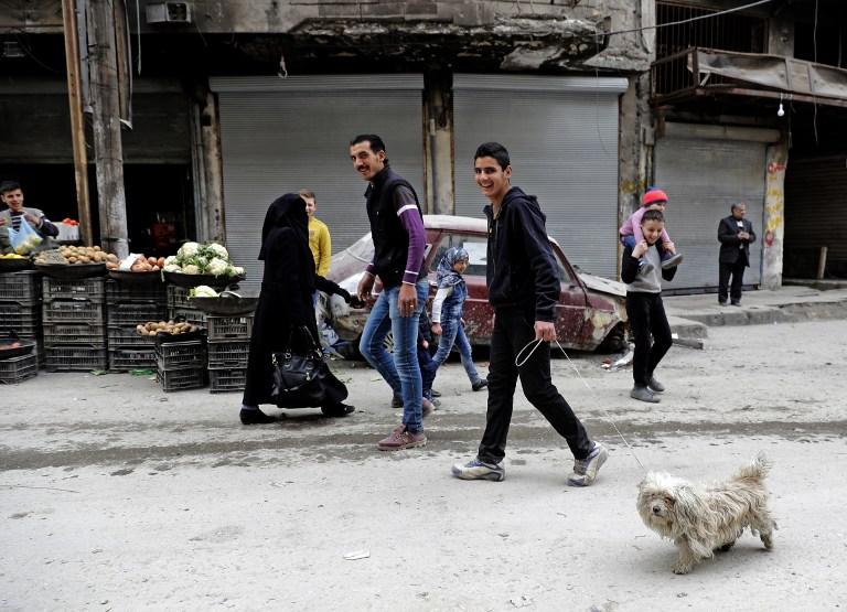 Un Syrien promène son chien dans le quartier de Chaar à Alep, autrefois aux mains des rebelles, le 10 mars 2017. (Crédit : Joseph Eid/AFP)