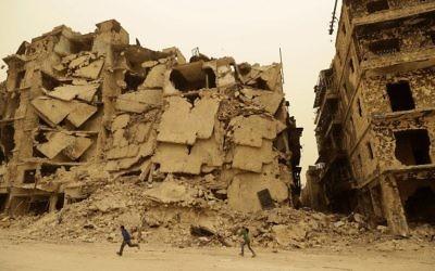 Des enfants syriens dans le quartier détruit de Kastal al-Harami à Alep, autrefois aux mains des rebelles, pendant une tempête de sable, le 10 mars 2017. (Crédit : Joseph Eid/AFP)