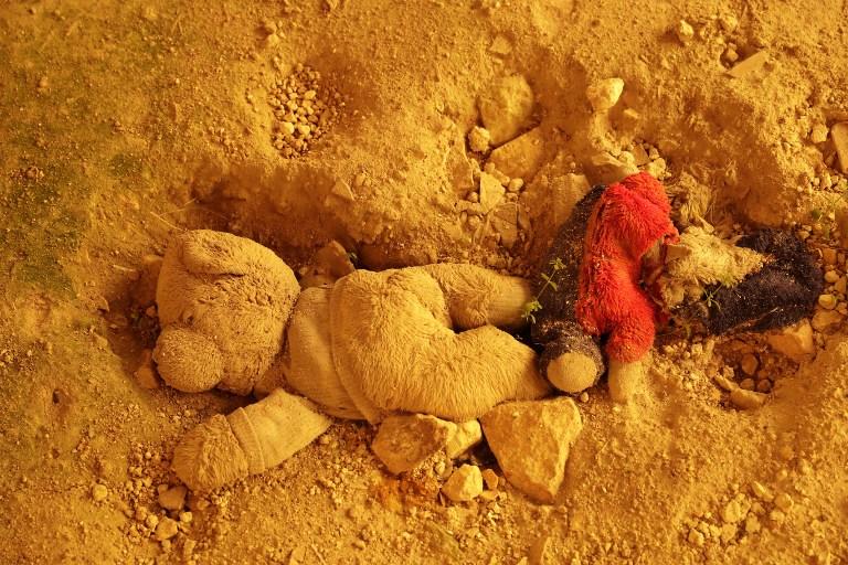 Un ours en peluche enterré dans le sol d'une maison du quartier de Bab Kinnisrin à Alep, autrefois aux mains des rebelles, pendant une tempête de sable, le 10 mars 2017. (Crédit : Joseph Eid/AFP)