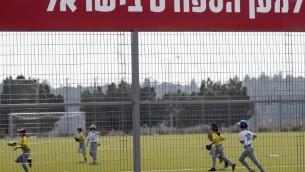 De jeunes Israéliens jouant un match de baseball entre les équipes de Modiin et de Jérusalem dans la ville israélienne de Modiin le 10 mars 2017 (Crédit : AFP Photo / Jack Guez)