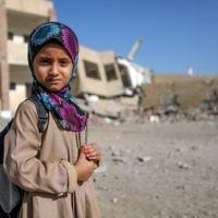 Une fillette yéménite devant une école détruite par une frappe aérienne dans la ville de Taëz, dans le sud du Yémen, le 16 mars 2017. (Crédit : Ahmad Al-Basha/AFP)