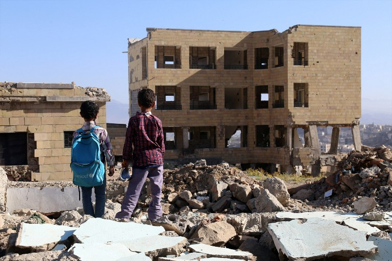 Des enfants yéménites devant une école détruite par une frappe aérienne dans la ville de Taëz, dans le sud du Yémen, le 16 mars 2017. (Crédit : Ahmad Al-Basha/AFP)